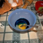 Mixing the egg with blue color.